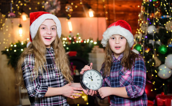 Girls sisters santa claus hat and clock. Kids lovely friends meet Christmas holiday. Festive atmosphere christmas day. New year countdown. Counting time. Magic moment is coming. Christmas almost here