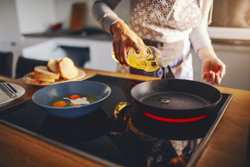 Cropped picture of woman in apron pouring oil in frying pan while standing next to stove. Breakfast preparation concept.