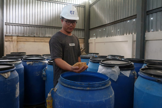 Worker from New Hope Liuhe displays pig feed ingredient for media at the company's feed plant in Ho Chi Minh city