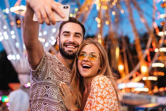 Positive loving couple walking outdoors in amusement park