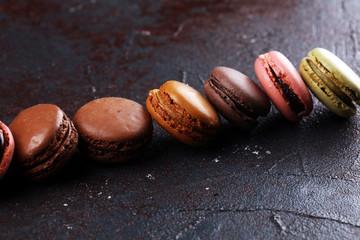 Foto auf Leinwand Macarons Sweet and colourful french macaroons or macaron on dark black background, Dessert.