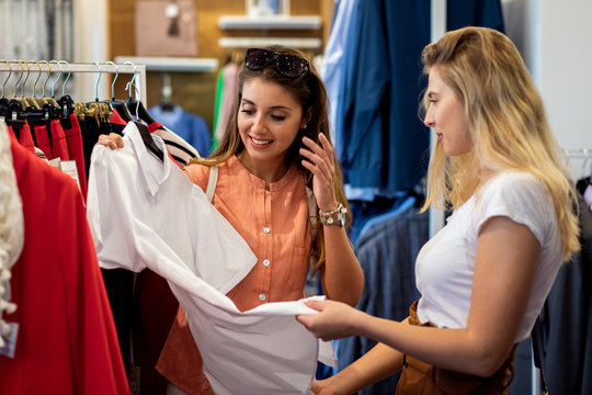 Two young female friends shopping together at clothes store.