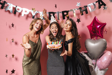 Image of beautiful party girls holding birthday cake with candles