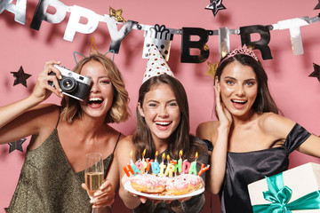 Image of party girls with retro camera holding birthday cake and gift box