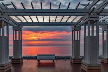lever de soleil au travers d'une pergola  sur la Promenade des anglais et la baie des anges à Nice