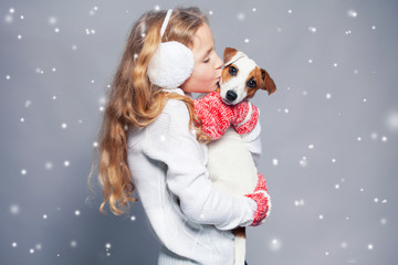 Girl with puppy in winter clothes