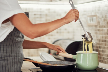 Cropped picture of mixed race woman in apron standing next to stove and making spaghetti.