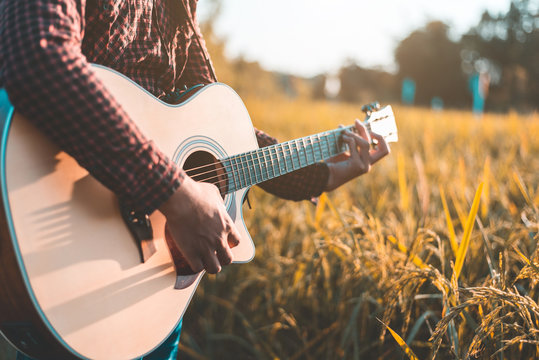 Country music, Man playing acoustic guitar in rice field, Focus on guitar strings