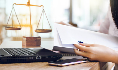 Female lawyer using mobile phone and laptop to find legal information