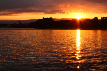 A sunset at a lake is coloring the water with yellow and golden colors. Location: Lake Geneva, Lausanne, Switzerland.