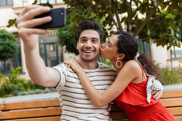 Image of excited young couple taking selfie photo on cellphone and kissing