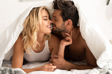 smiling couple going to kiss under sleeping sheets in the morning