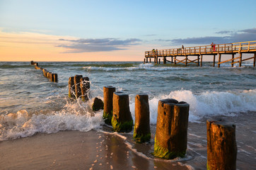 Wooden pier and breakwater during sunset over the Baltic Sea, Uniescie, Poland.