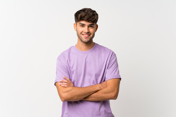 Young handsome man over isolated white background keeping the arms crossed in frontal position