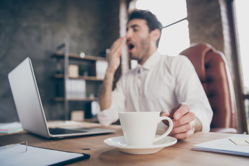 Profile side low angle view photo of tired middle eastern marketer man have lots work yawn want sleep take mug with hot beverage americano sit table chair in loft office