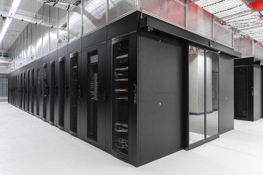 Shot of a long hallway full server racks in a modern data center. Server room.