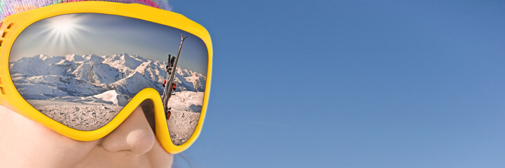 Close up of a girl with a ski mask reflecting a snowy mountain and ski slope, blue sky panoramic background