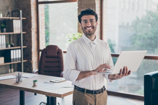 Portrait of positive confident smart middle eastern entrepreneur man hold laptop using feel success have online seminar training self-development in loft work office