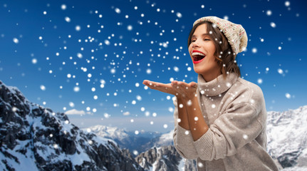 christmas, season and people concept - happy smiling young woman in knitted winter hat and sweater sending air kiss over snow and alps mountains background