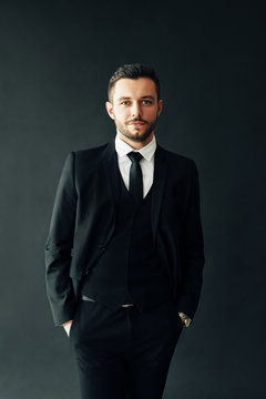 Portrait of elegant young man in suit on black background