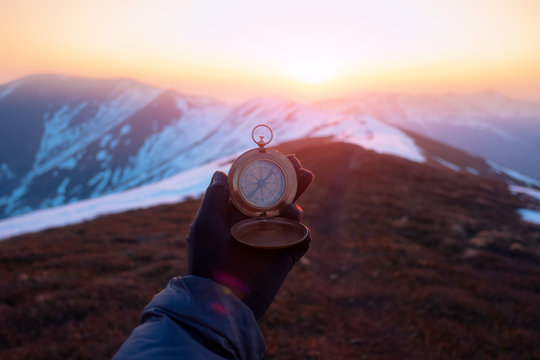 Man with retro compass in high snowy mountains on sunrise time. Travel concept. Landscape photography