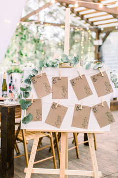 Decorated seating plan for wedding guests in woodent tent restaurant outdoors. Original rustic wooden board with guest list