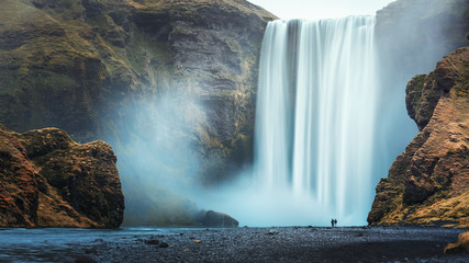 Photo sur Aluminium Taupe Couple of tourist near famous Skogafoss waterfall, Iceland