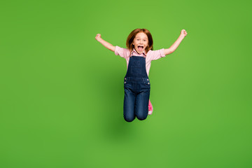 Full length photo of cheerful pretty little schoolchild jumping high rejoicing summer holidays...