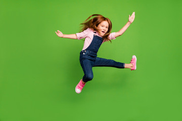 Full length photo of cheerful funny pretty little schoolchild jumping high fighting exercises training wear casual denim overall pink shirt isolated green background