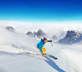 Fototapete - Young man skier running down the slope in Alpine mountains