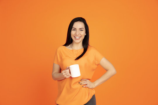 Caucasian young woman's portrait on orange studio background. Beautiful female brunette model in shirt. Concept of human emotions, facial expression, sales, ad. Copyspace. Drinking coffee or tea.