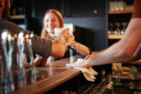 Bartender wiping bar counter while couple leaning on counter and making a toast with beer. Selective focus on hand.