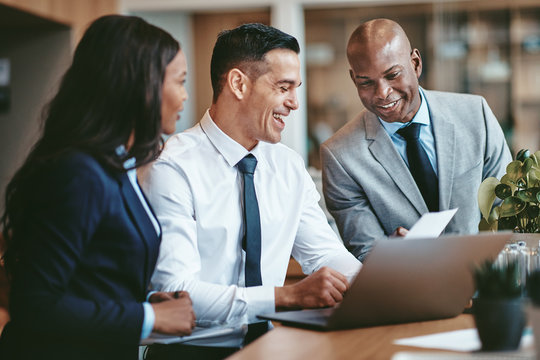 Diverse businesspeople laughing while working together at an off