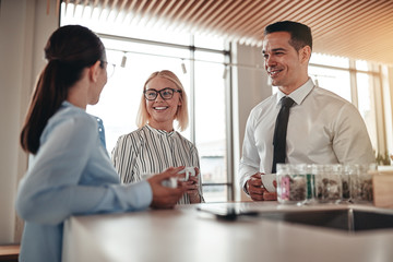 Smiling businesspeople talking together over coffee in their off