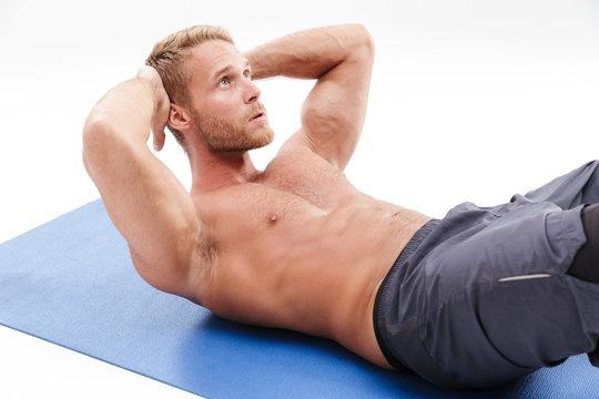 Confident attractive sportsman doing core exercise