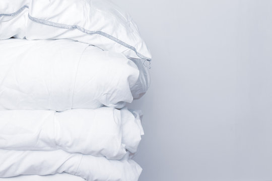 Pile of white bedding items, pillows and a blanket on white background with copy space