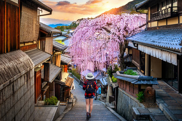Wall Mural - Woman traveler with backpack walking at Historic Higashiyama district in spring, Kyoto in Japan.