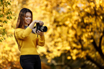 beautiful smiling woman photographer with camera takes pictures in park in autumn. copy space