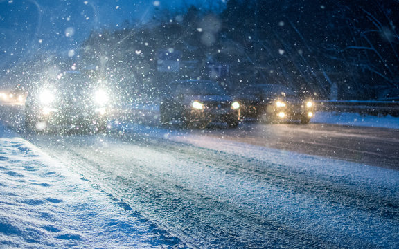 Headlights of cars at night on a snowy road in winter.