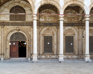 Wrought iron decorated Windows and wooden ornate door over white alabaster decorated wall leading to Mosque of Muhammad Ali Pasha - Alabaster Mosque - Citadel of Cairo, Egypt