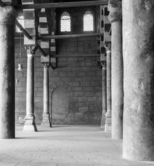 Black and white shot of corridor surrounding the courtyard of public historical Mosque of al Sultan al Nasir Muhammad Ibn Qalawun situated in the Citadel of Cairo, Egypt