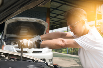 Hands of mechanic repairing the engine of the special keys (wrenches and ratchets). Professional mechanic in gloves working in a car service.