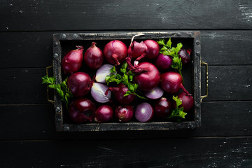 Purple onion in wooden box on black background. Top view. Free copy space.