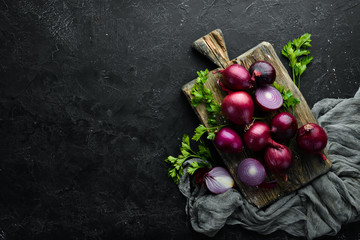 Fresh red onions on black background. Top view. Free copy space.