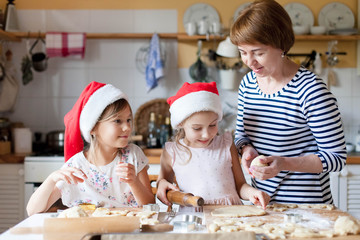 Family is cooking Christmas gingerbread cookies together in cozy home kitchen for dinner. Kids and grandmother are preparing holiday food. Girls help woman. Lifestyle moment. Children chef concept