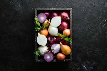 Fresh ripe onions in wooden box on black background. Top view. Free copy space.