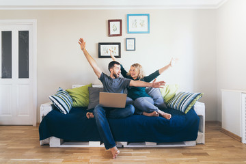 Young couple doing shoppings online on the sofa at home with laptop, happy and smiling