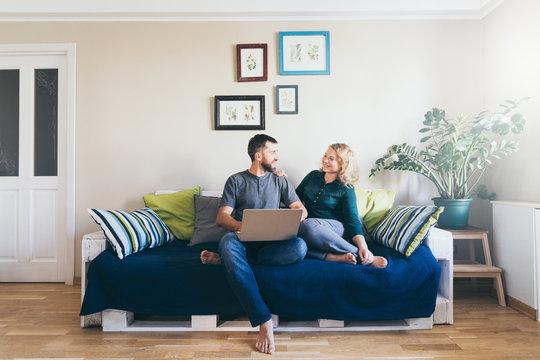 Young couple doing shoppings online on the sofa at home with laptop, looking at each other and smiling