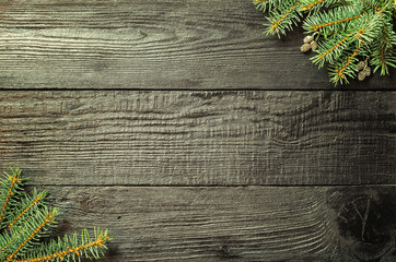 Christmas fir tree branches and pine cones on wooden dark, black background.