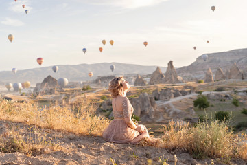 woman is watching on scenery view with rising balloons on sunrise. Girl in gorgeous pink long dress sit on hill looking at large number of air balls. Fabulous Cappadocia mountains landscapes Turkey Wall mural